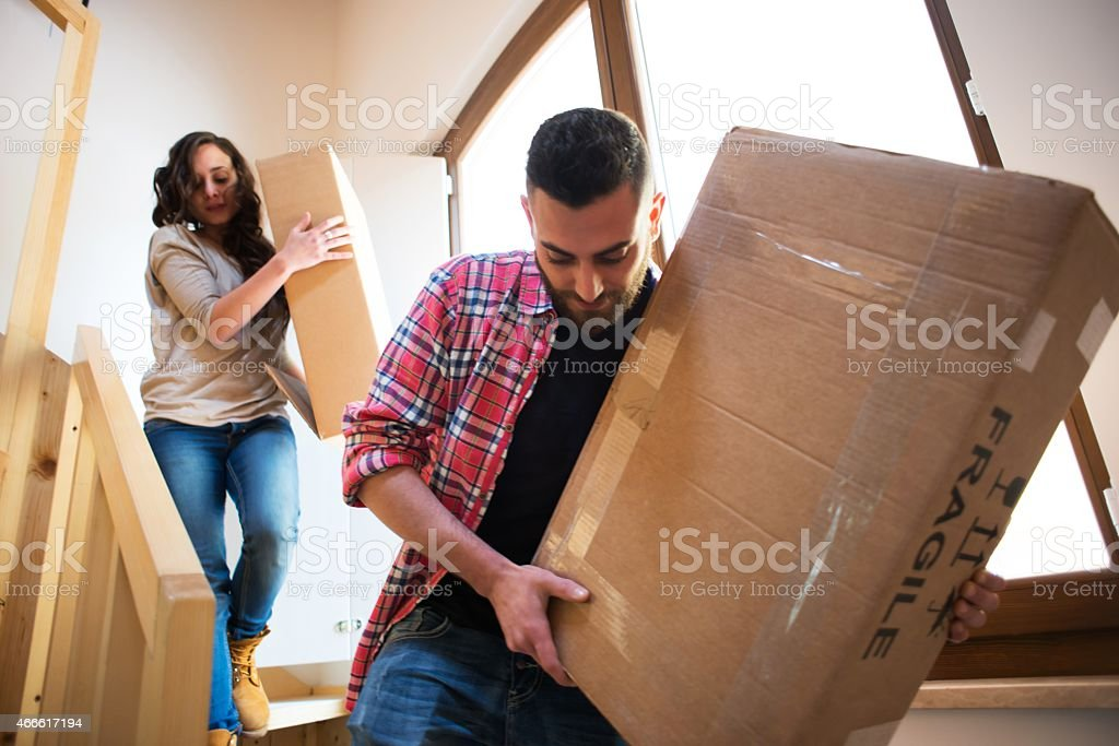 Couple Walking down the Stairs with a box. stock photo
