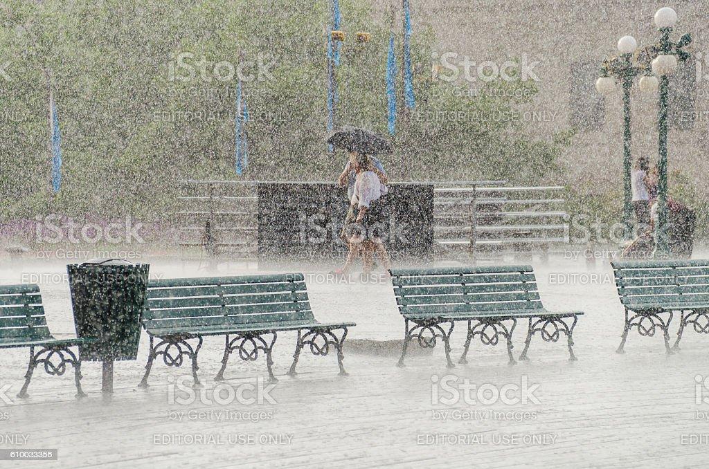 Couple walking in heavy rain stock photo
