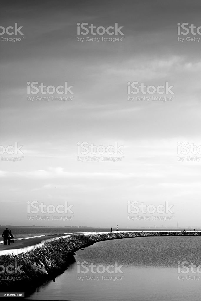 Couple walking in the middle of a river stock photo