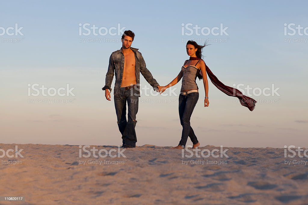 Couple walking in the sand royalty-free stock photo