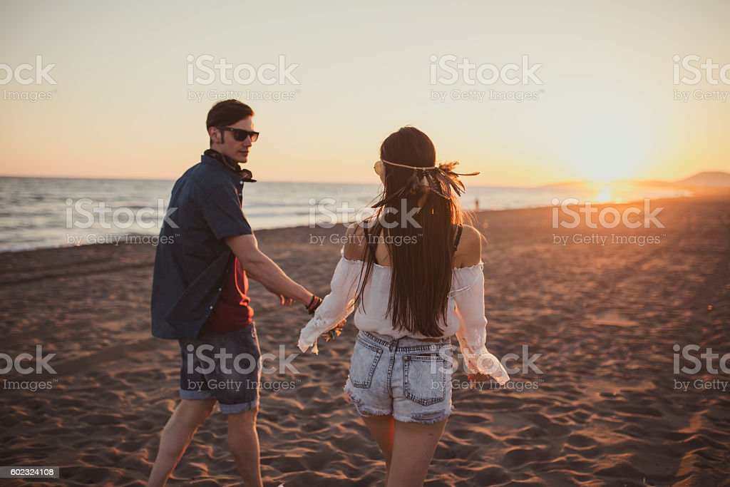 Couple walking in the sunset on the beach stock photo