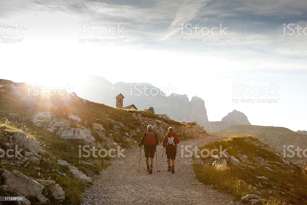 Couple walking into the sunset royalty-free stock photo