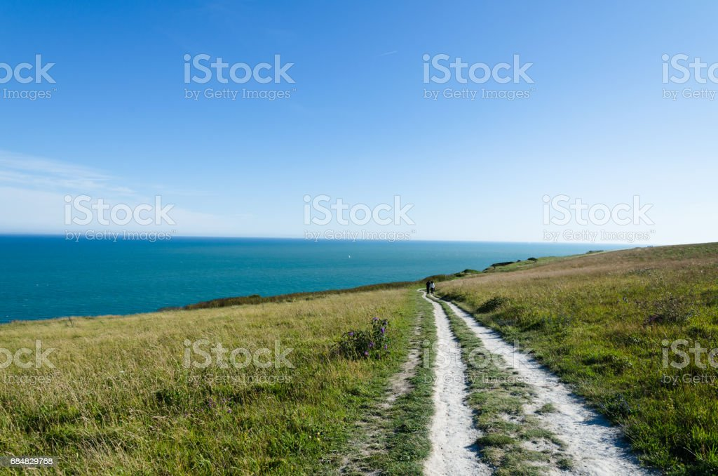 Couple walking on a footpath towards the sea stock photo