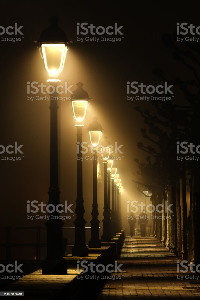 couple walking on dark street illuminated with streetlamps stock photo