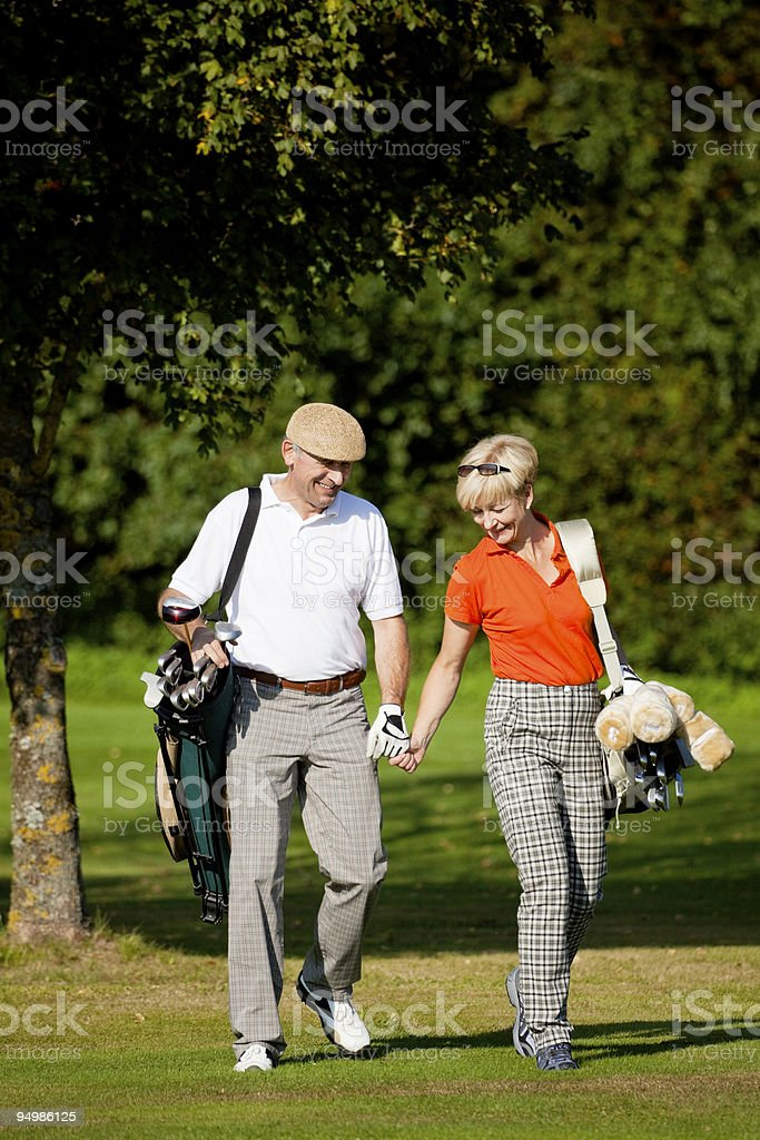 Couple walking on golf course holding hands royalty-free stock photo