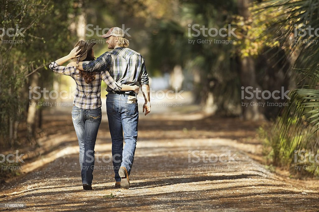 Couple Walking On Path Amid Trees royalty-free stock photo
