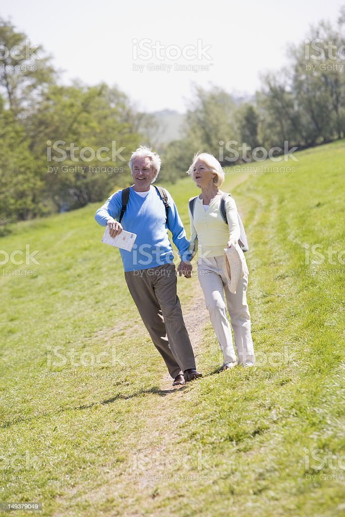 Couple walking on path in park holding hands and smiling royalty-free stock photo
