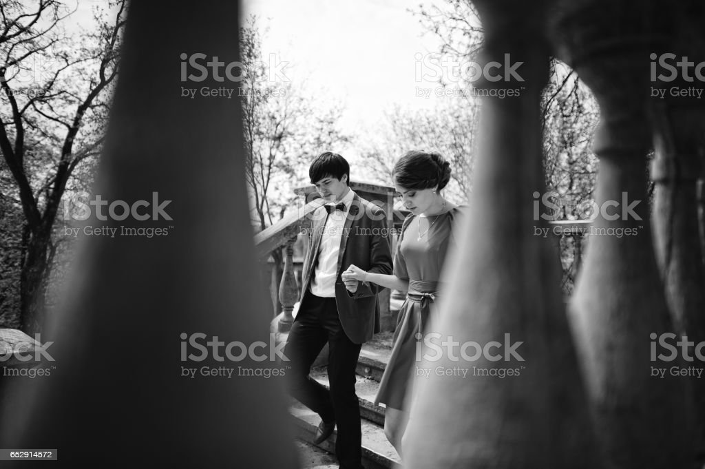 Couple walking on stairs holding hands. Stylish man at velvet jacket hold hand girl in red dress. Hidden view stock photo