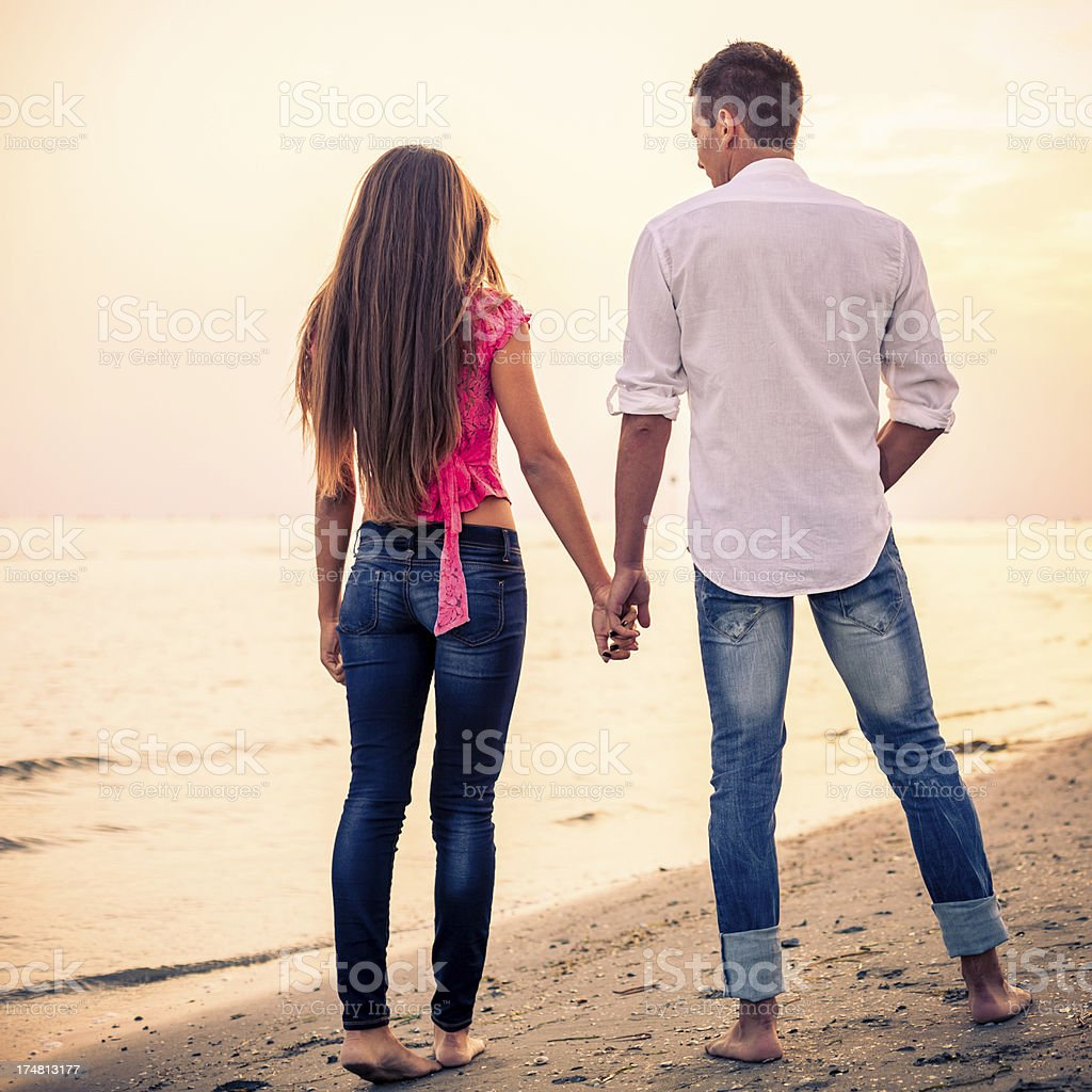 Couple walking on the beach at Sunset royalty-free stock photo
