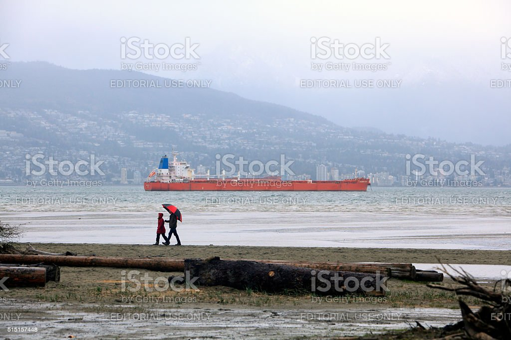 Couple Walking On Vancouver Beach In The Rain Past Freighter stock photo