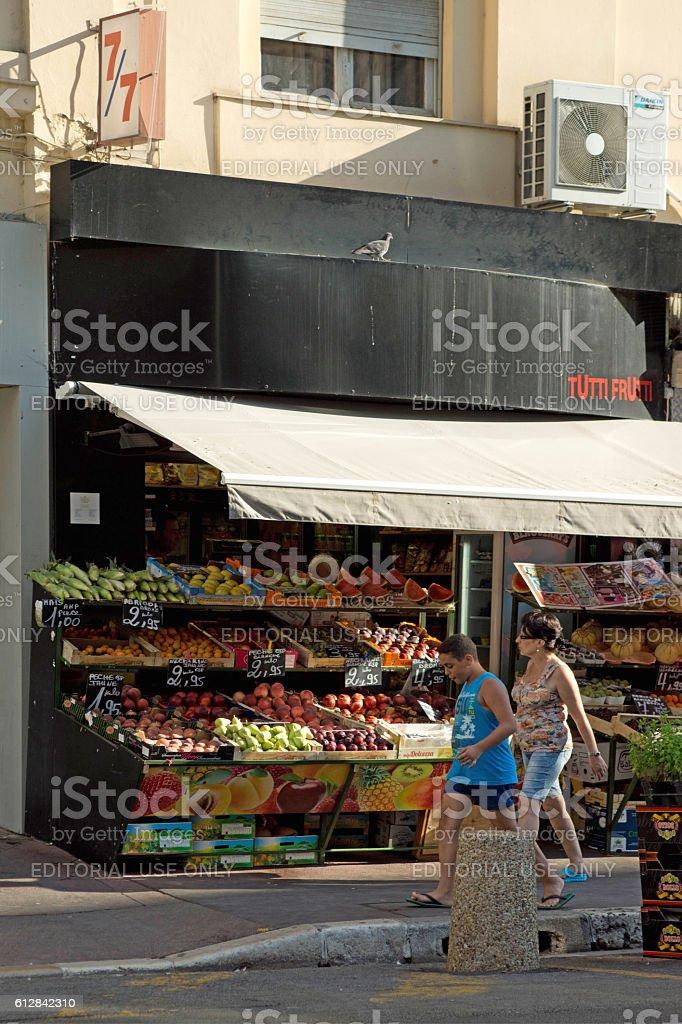 Couple walking past a Fruit shop stock photo