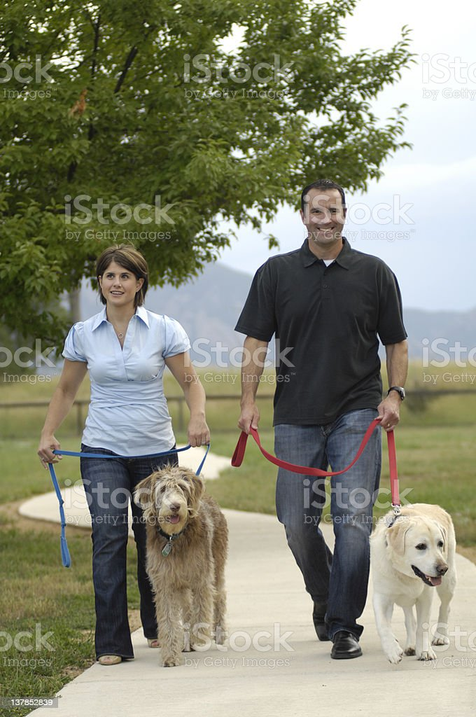 Couple Walking their Dogs royalty-free stock photo