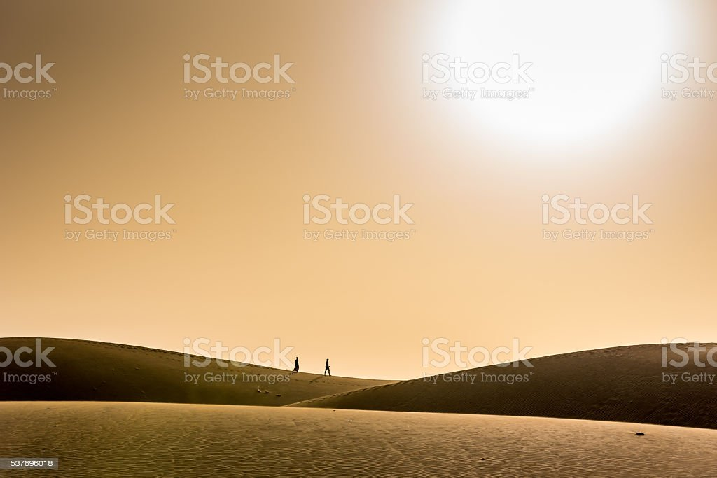 Couple walking together in desert with sunset stock photo