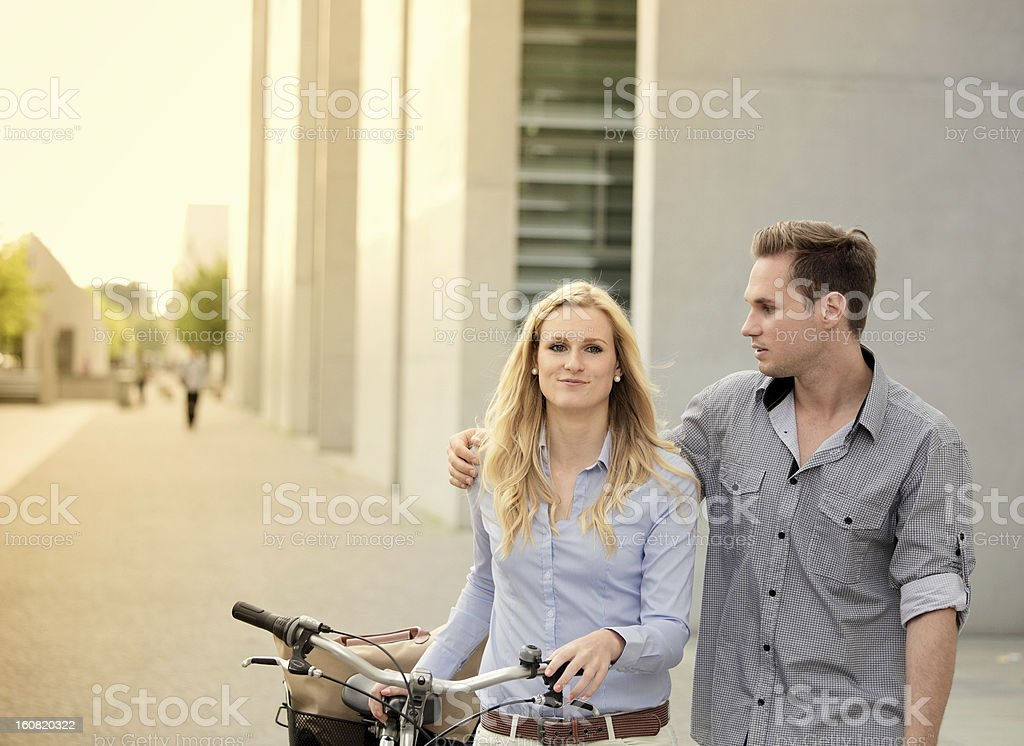 Couple walking together past building royalty-free stock photo