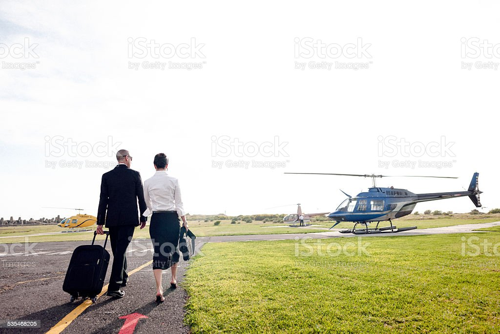 A couple walking towards a helicopter stock photo