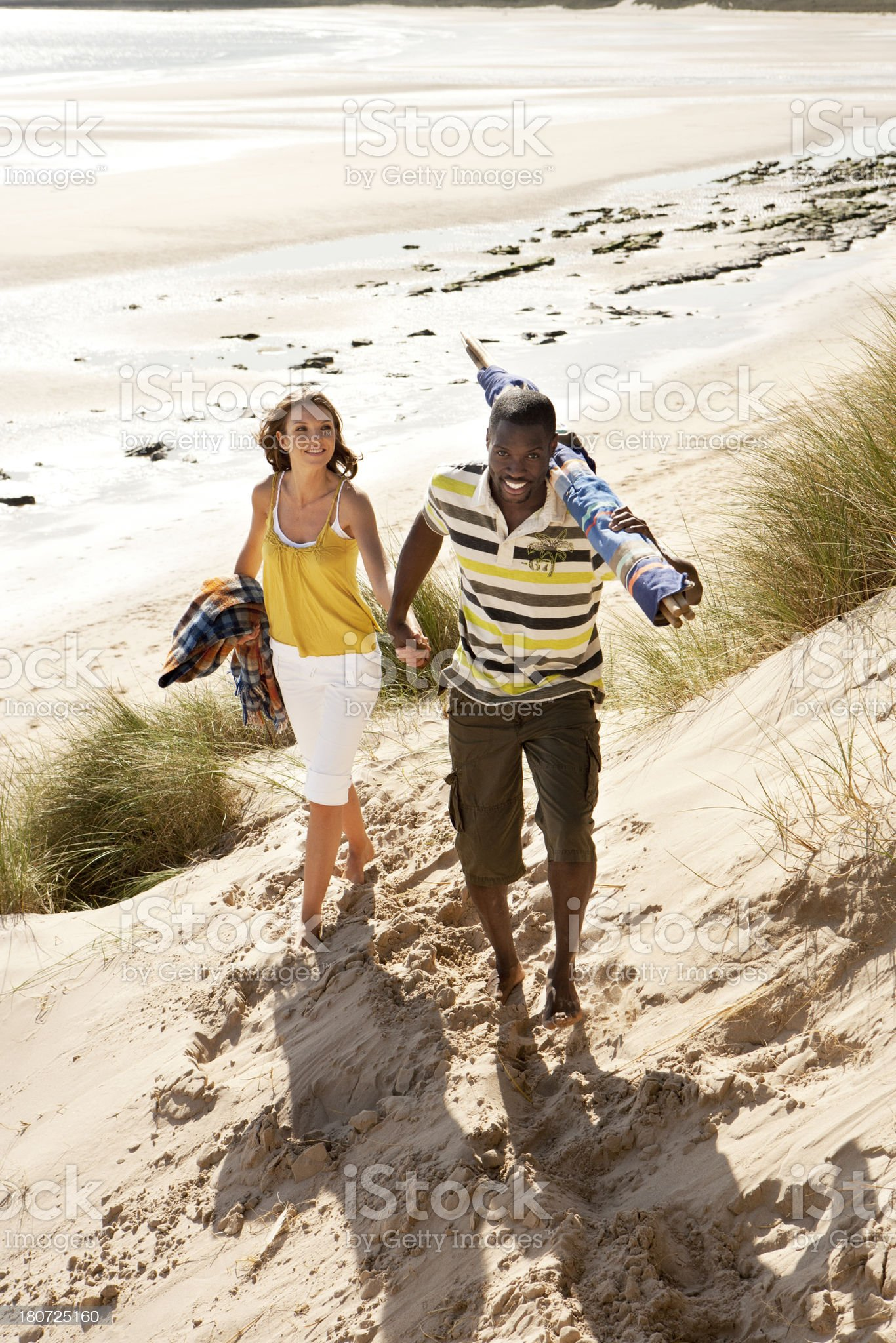 Couple walking up a dune royalty-free stock photo