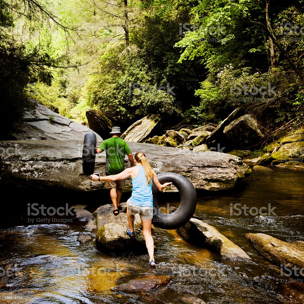 Couple Walking Up Stream With Inner Tubes stock photo
