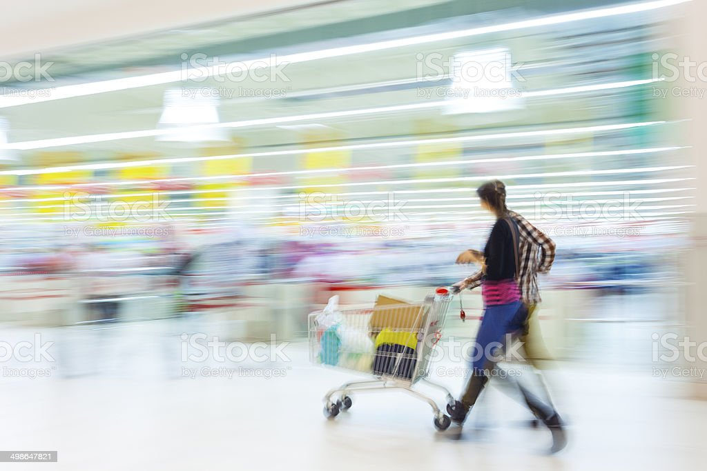 Couple Walking With Shopping Cart in Mall stock photo