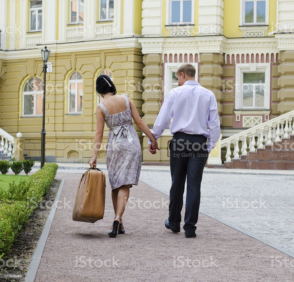 Couple walking with woman carrying luggage royalty-free stock photo