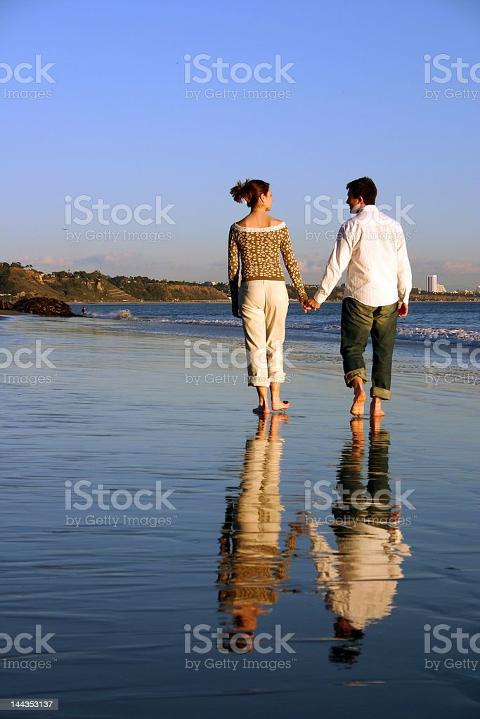 Couple walks down the beach holding hands royalty-free stock photo