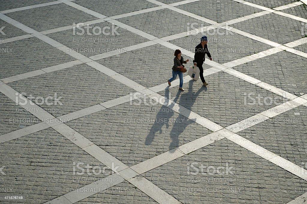 Couple Walks with Shadows on Stone Plaza Paris France stock photo
