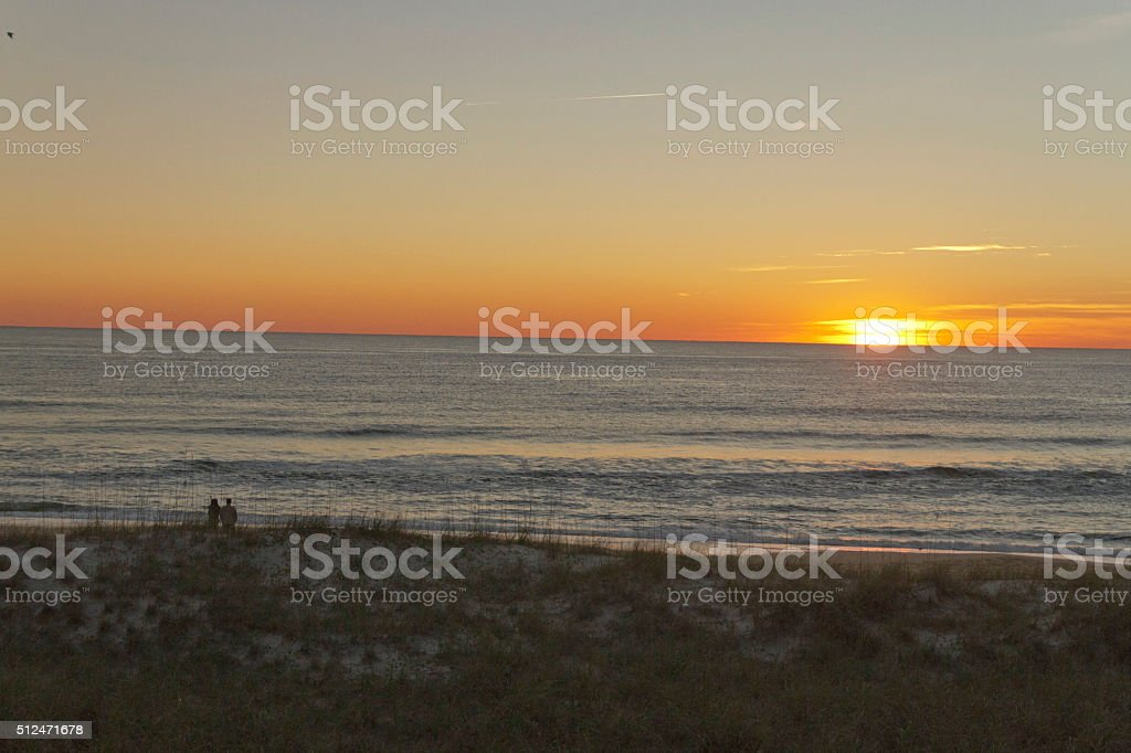 Couple Watch an Ocean Sunset Together stock photo