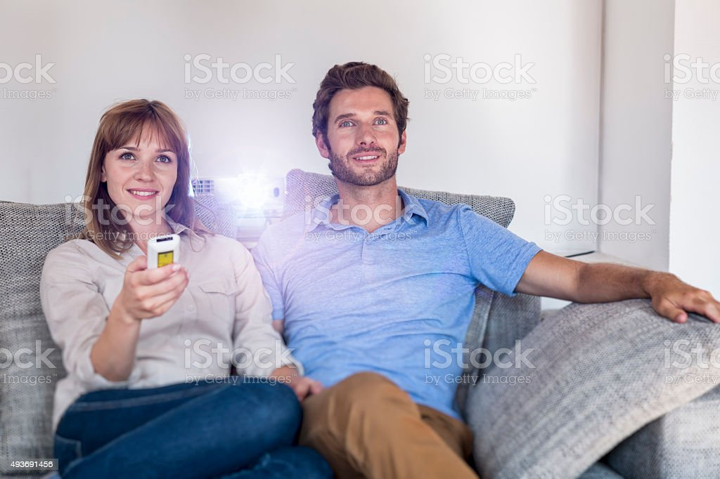 Couple watching a movie with a video projector on sofa stock photo