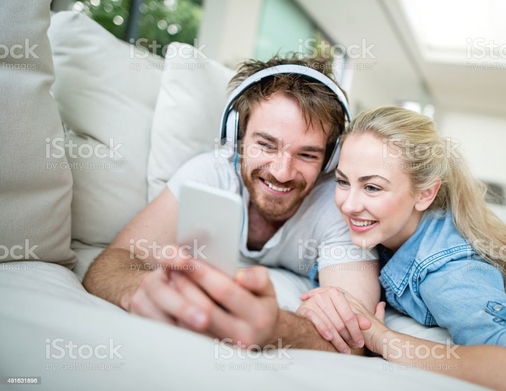 Couple watching a video on a smart phone stock photo