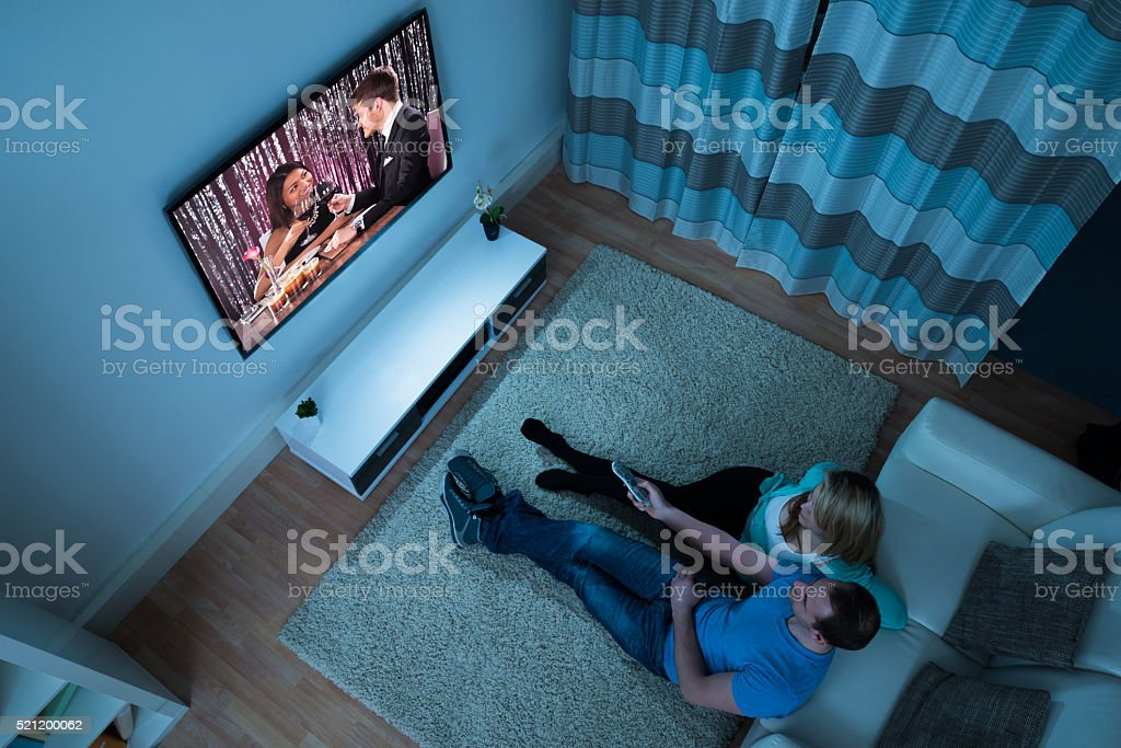 Couple Watching Movie In Living Room stock photo