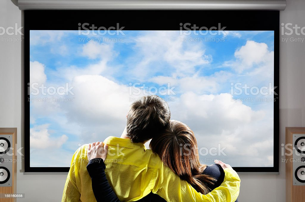 Couple watching movies on large screen, home theater system stock photo