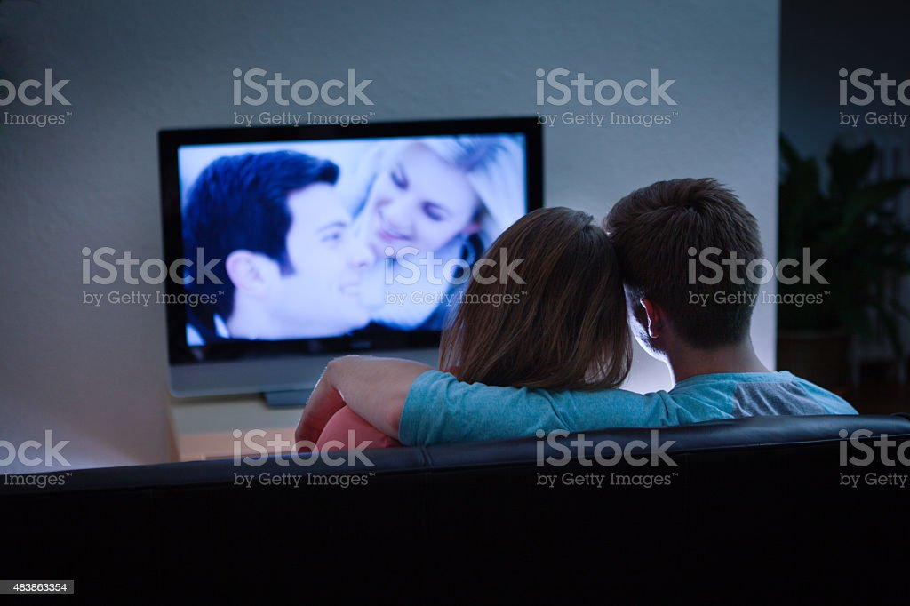 A young Caucasian couple at home watching a romantic program show on...