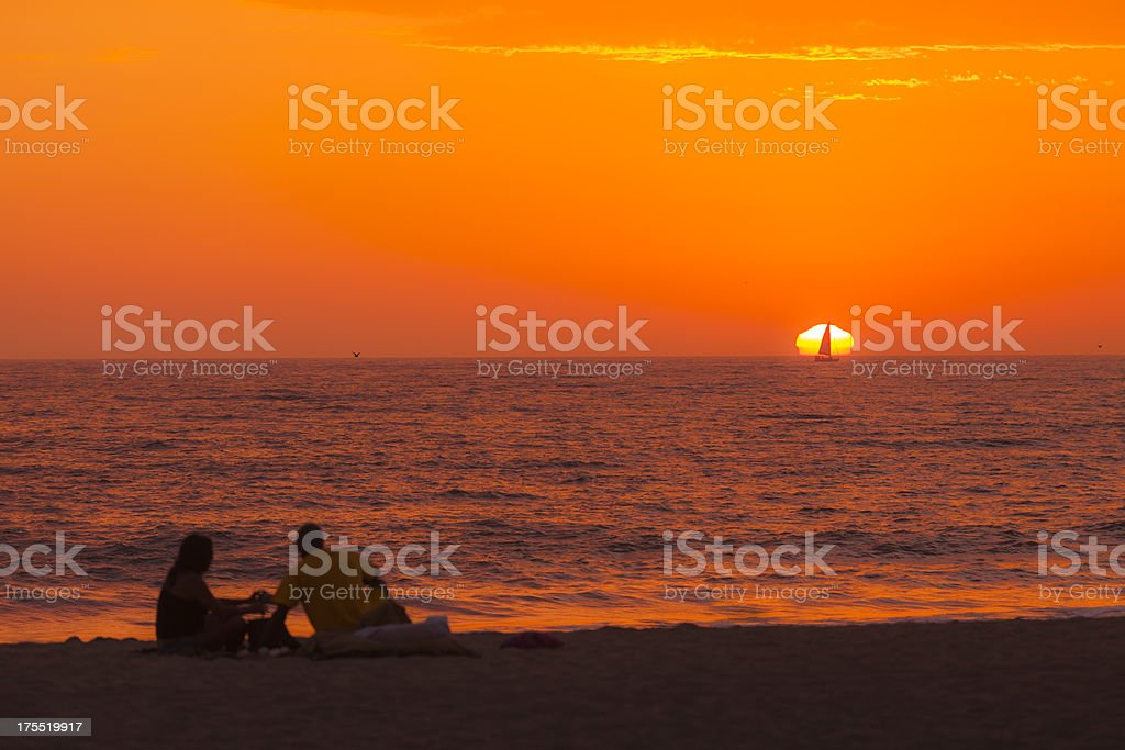 Couple watching sailboat pass through sun setting on horizon stock photo