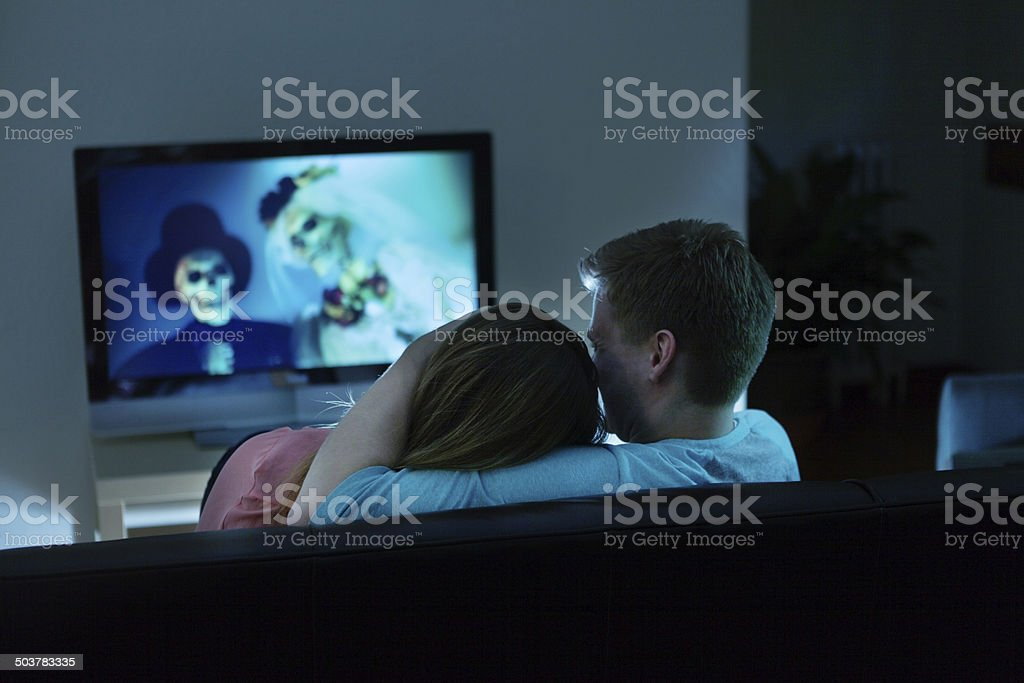 Couple Watching Scary Halloween Movie Together on TV stock photo