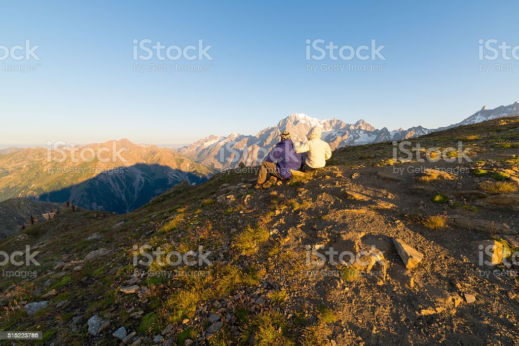 Couple watching sunrise over Mont Blanc summit stock photo