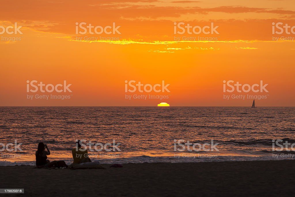 Couple watching sunset and sailboat in ocean. stock photo