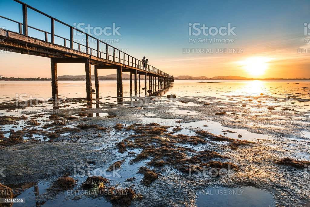 Couple watching sunset on pier in Búzios royalty-free stock photo