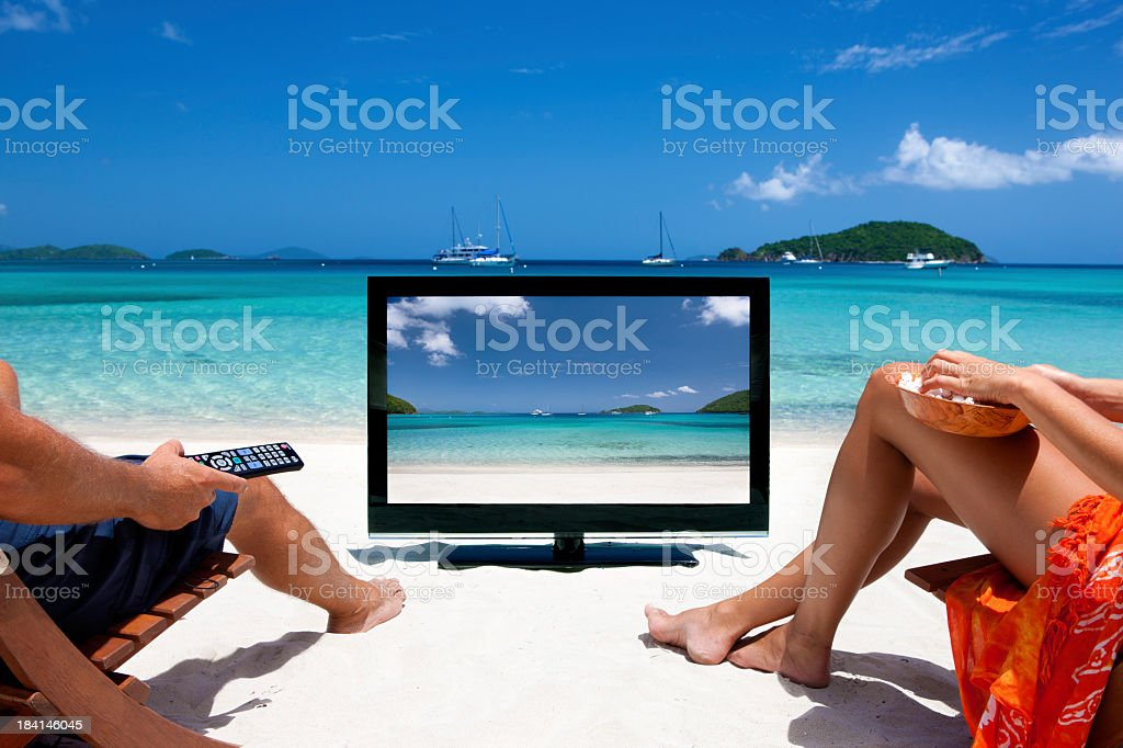 couple watching television at a tropical Caribbean beach stock photo