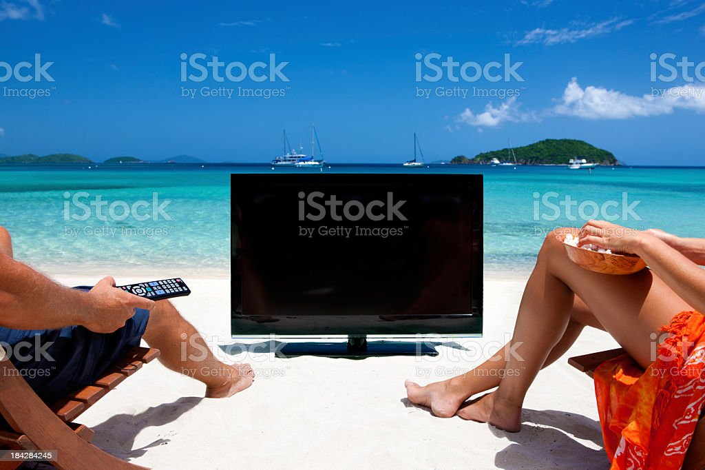 couple watching television at a tropical Caribbean beach royalty-free stock photo