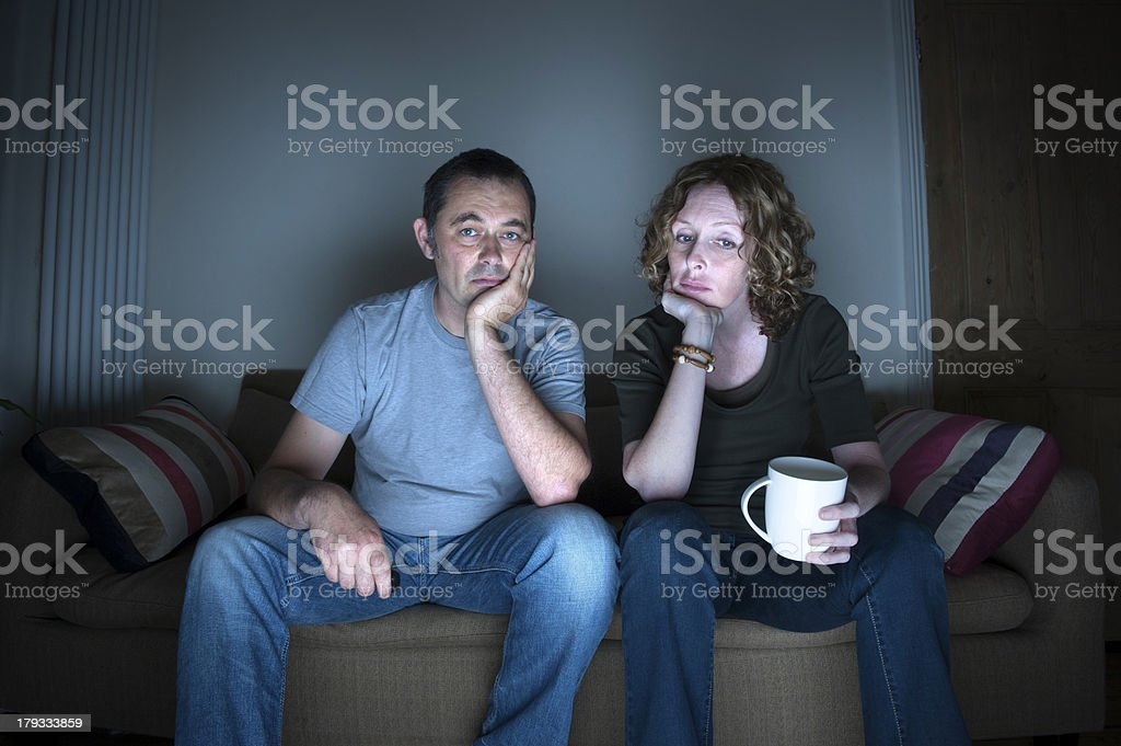 couple watching television bored stock photo