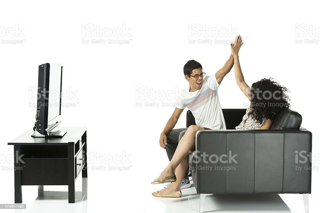 Couple watching television, giving high five royalty-free stock photo
