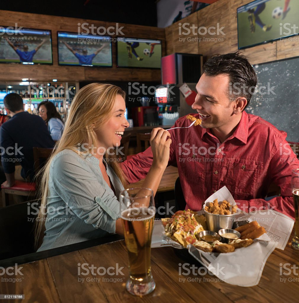 Couple watching the game at a sports bar and eating stock photo
