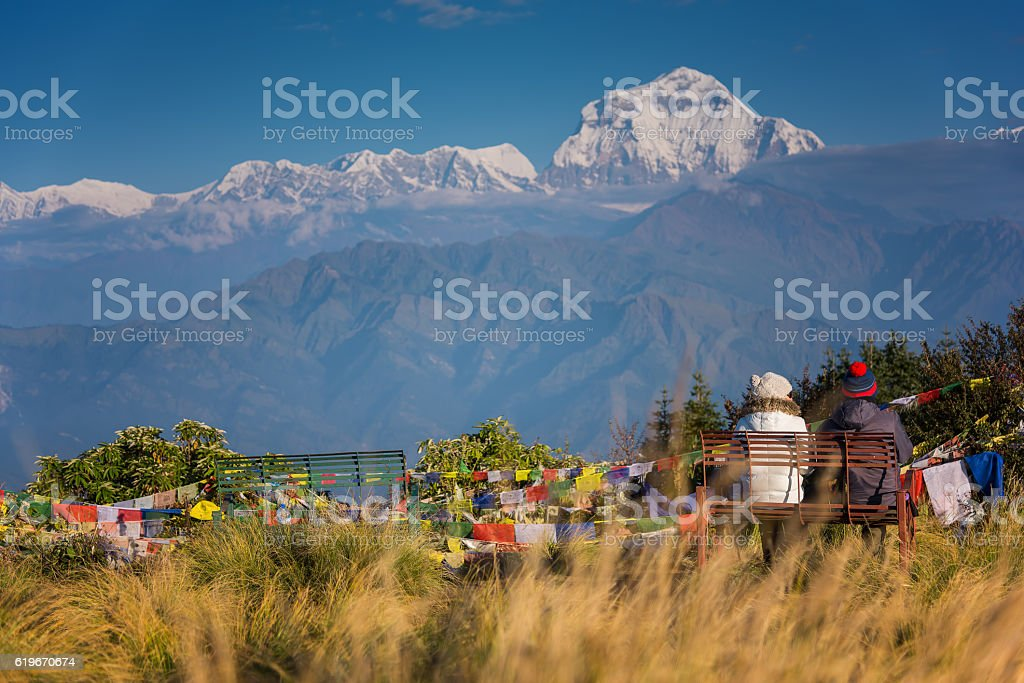 Couple watching the Mt. Dhaulagiri (8,172m) from Poonhill, Nepal. stock photo