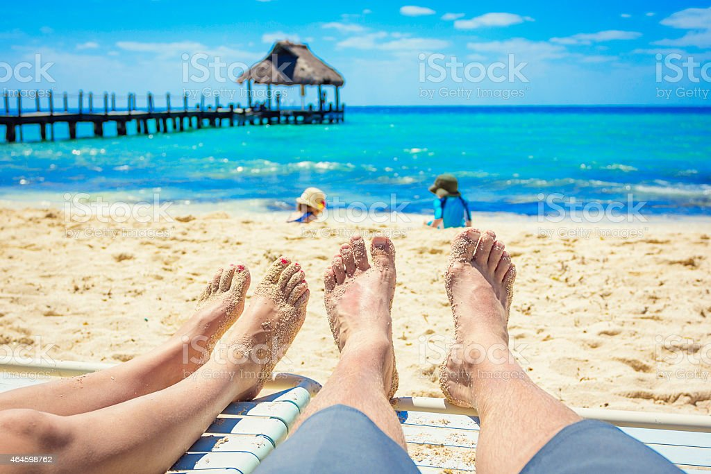 Couple watching their kids playing on the beach on vacation stock photo