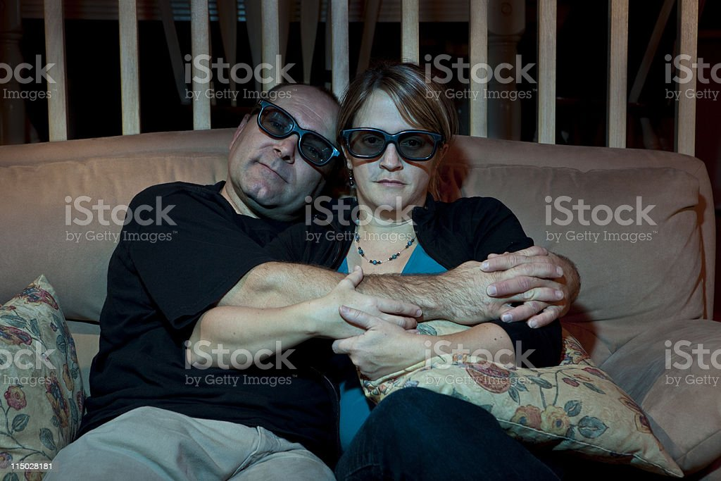 Couple watching TV and hugging cuddling 3D glasses stock photo