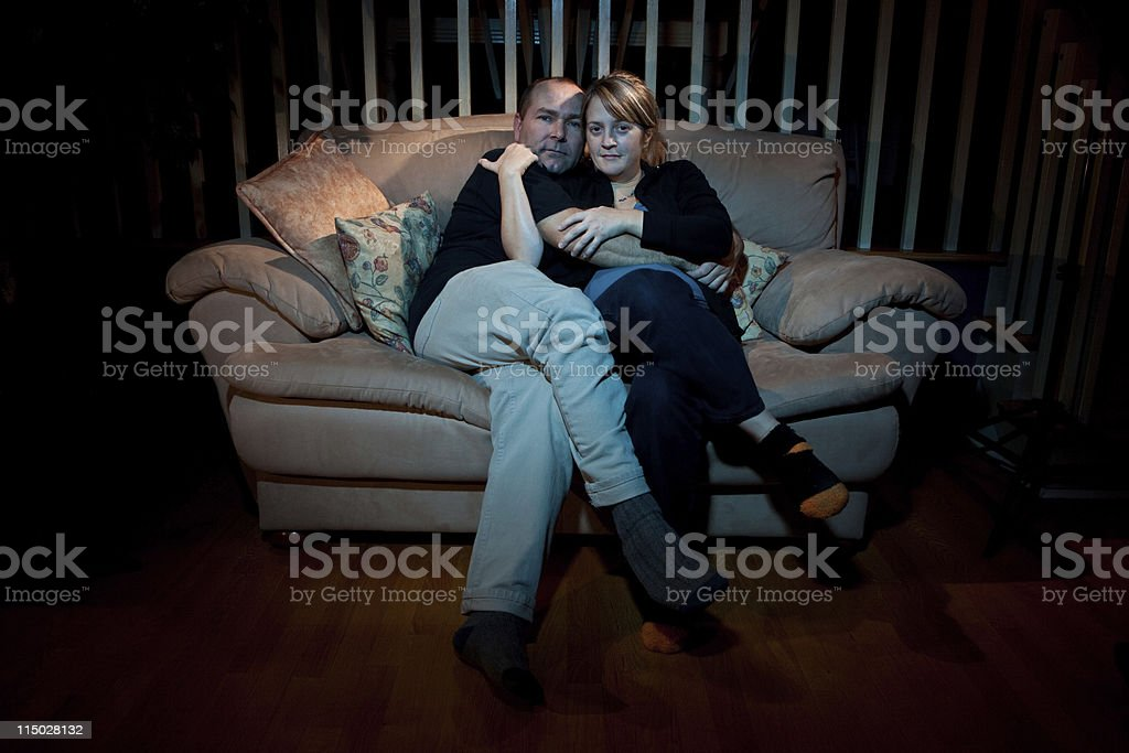 Couple watching TV and hugging cuddling stock photo