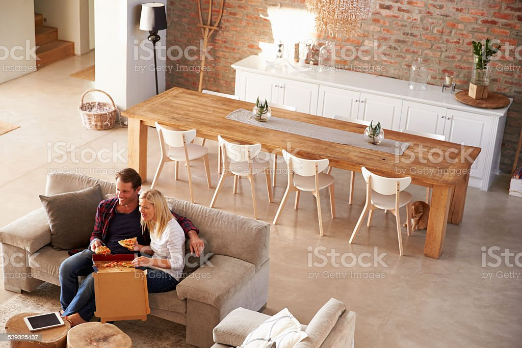Couple watching TV at home and eating pizza stock photo