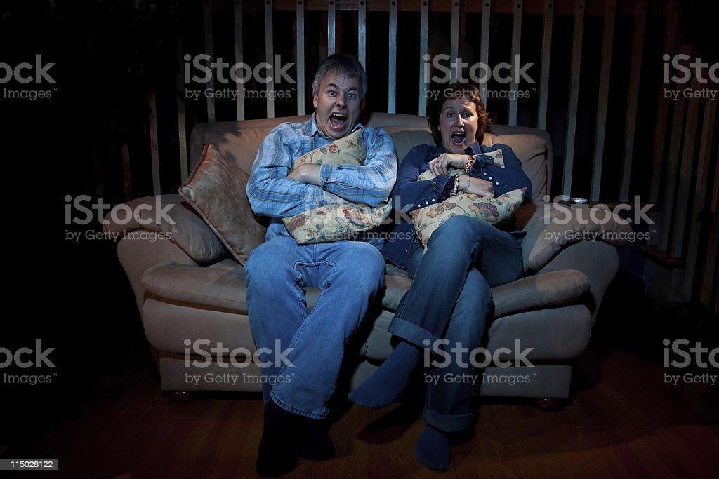 Couple watching tv horror movie stock photo