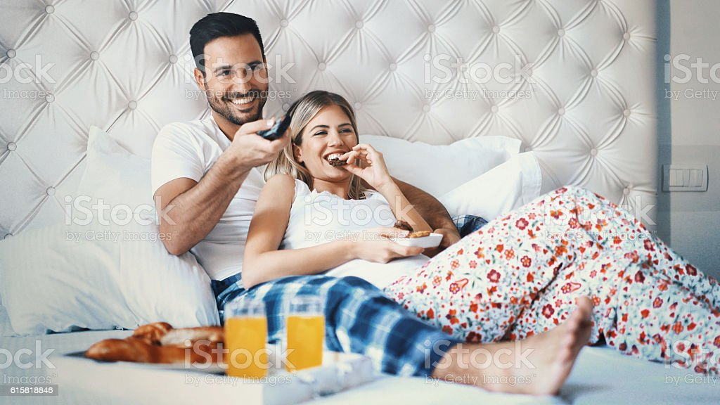 Couple watching tv in bedroom. stock photo