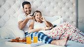 Couple watching tv in bedroom.