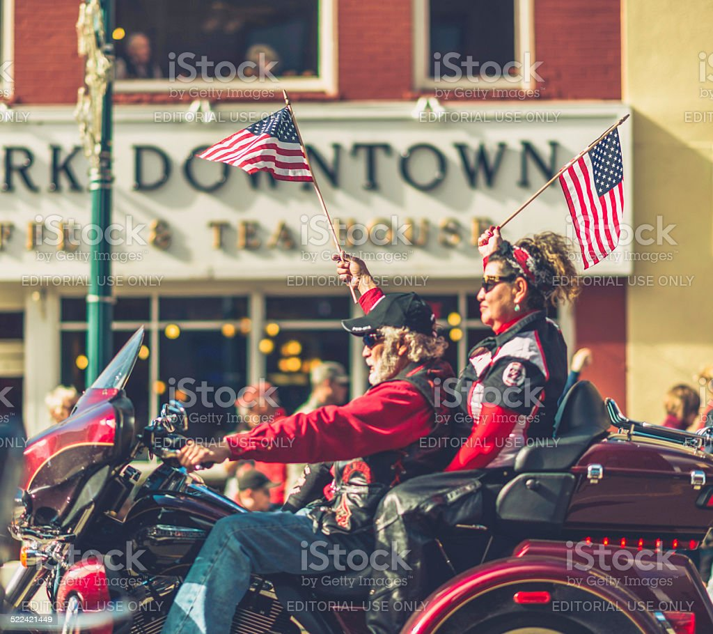 Couple waving American flags on motorcycle in Veterans Day Parade stock photo